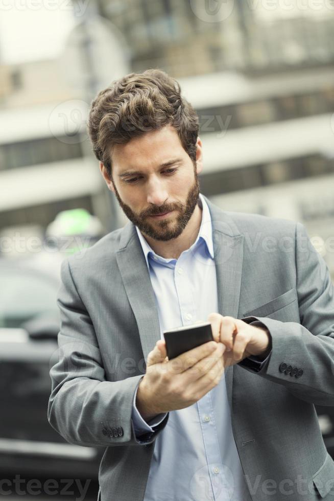 homem pede um táxi em seu telefone móvel foto