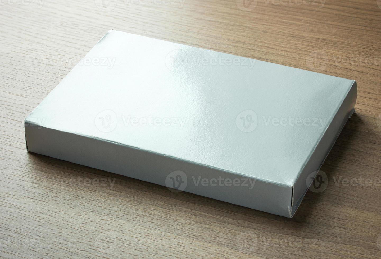 caixa de papel cinza em branco sobre fundo escuro de madeira foto