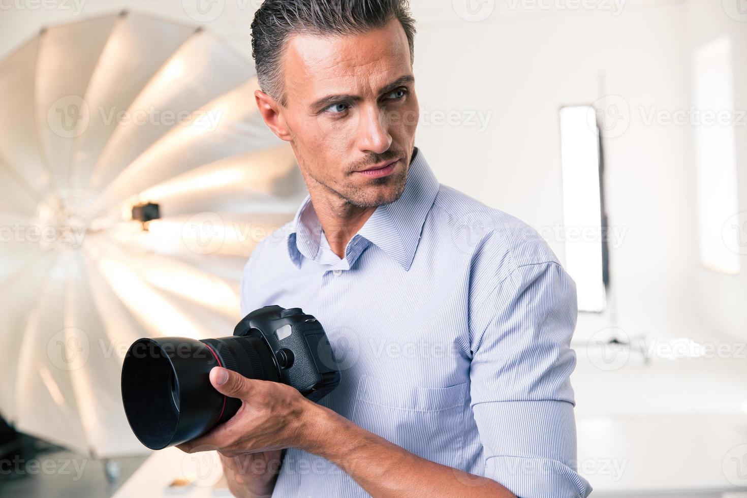 fotógrafo, segurando a câmera e olhando para longe foto
