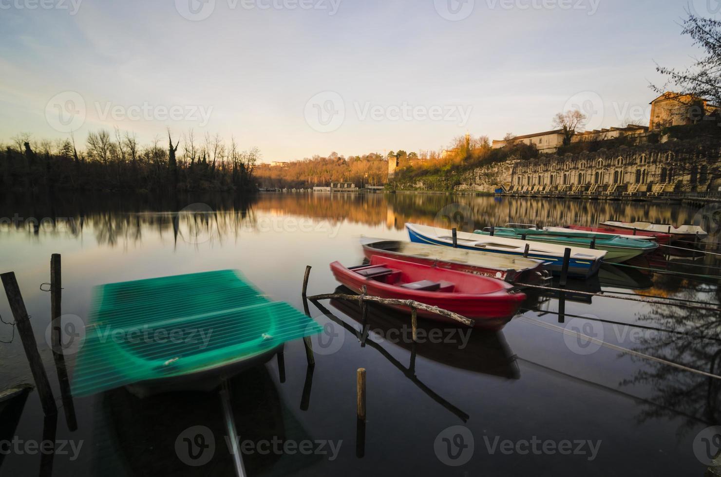 barcos coloridos e barragem de pedra velha refletida na água foto