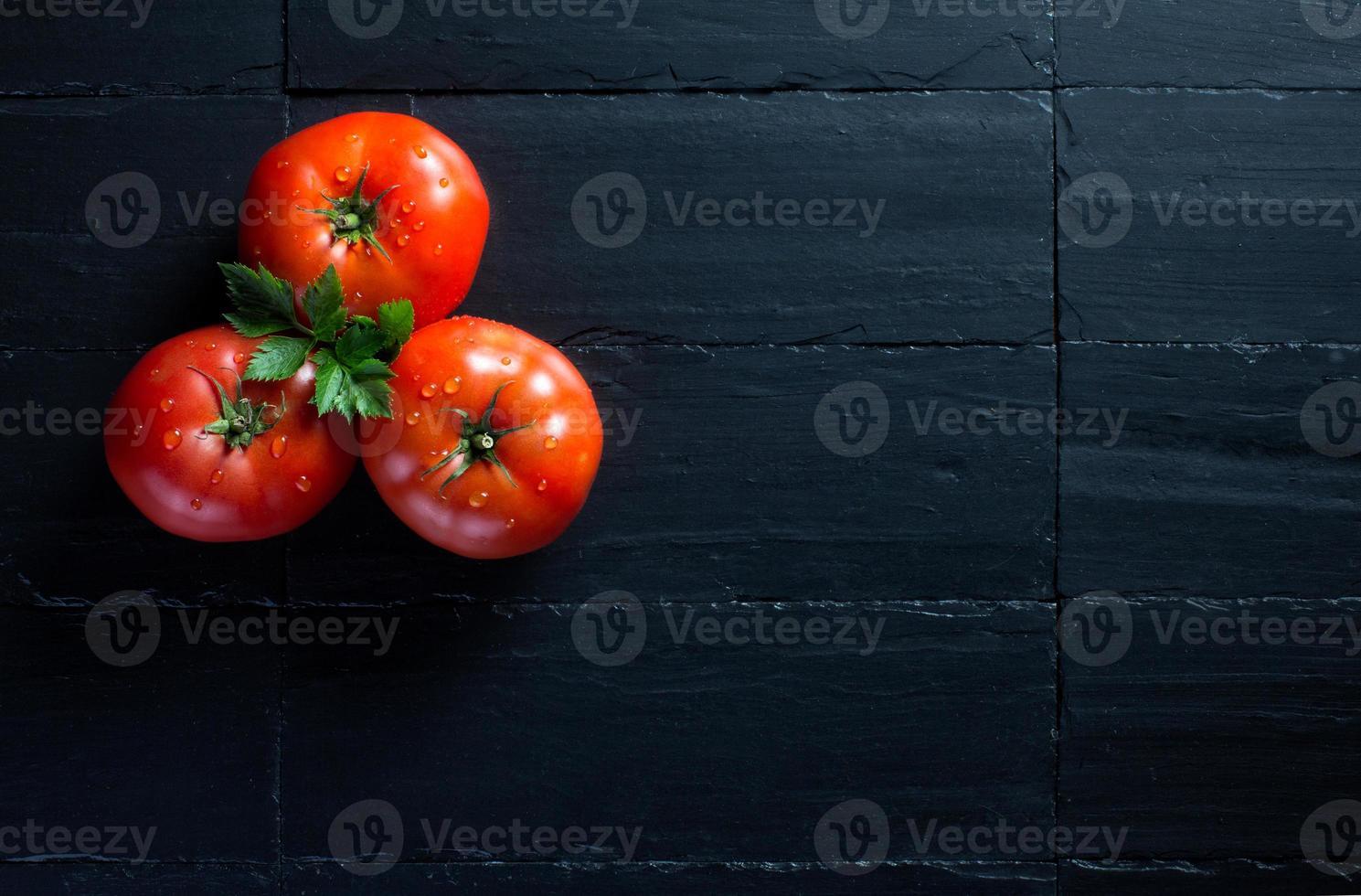tomates frescos e saudáveis sobre ardósia preta foto