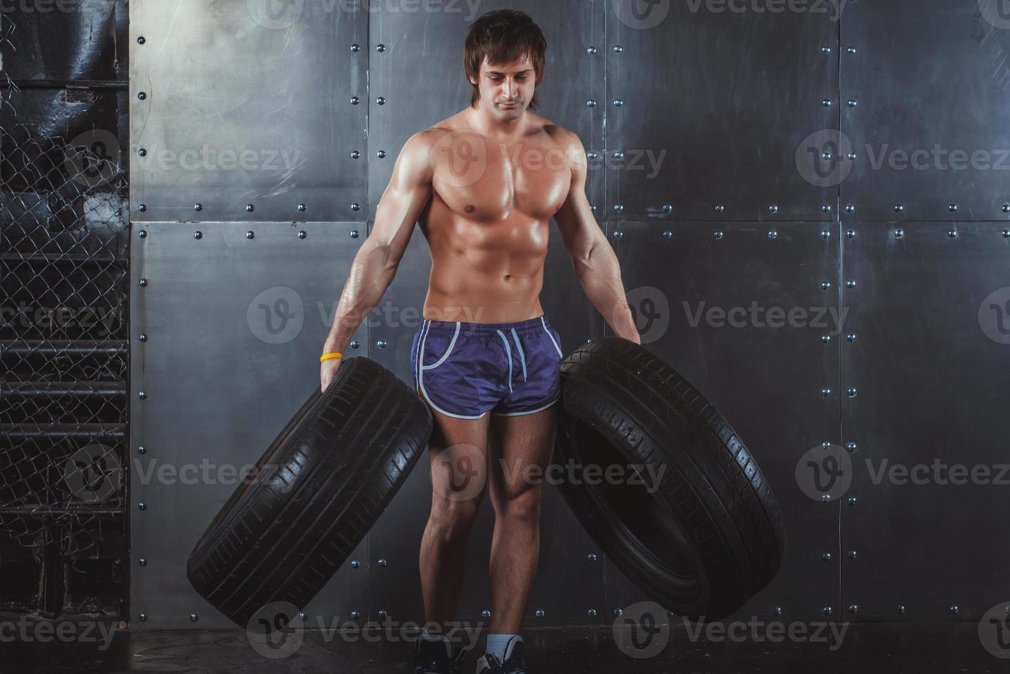 homem de ginásio atleta atleta malhando exercitar-se com pneus foto