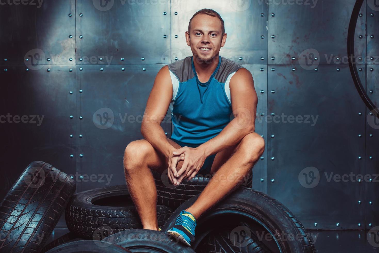 esportista sentado na máquina de pneus. conceito de academia, saúde foto