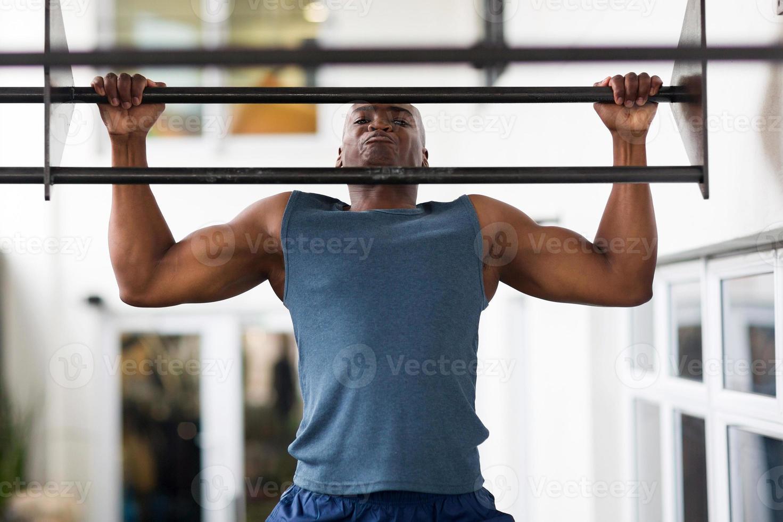 homem Africano fazendo flexões em um bar foto