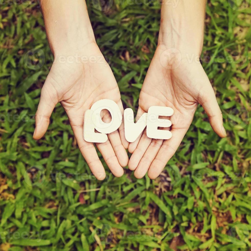 """foto de estilo amador da palavra """"amor"""" nas duas mãos"""