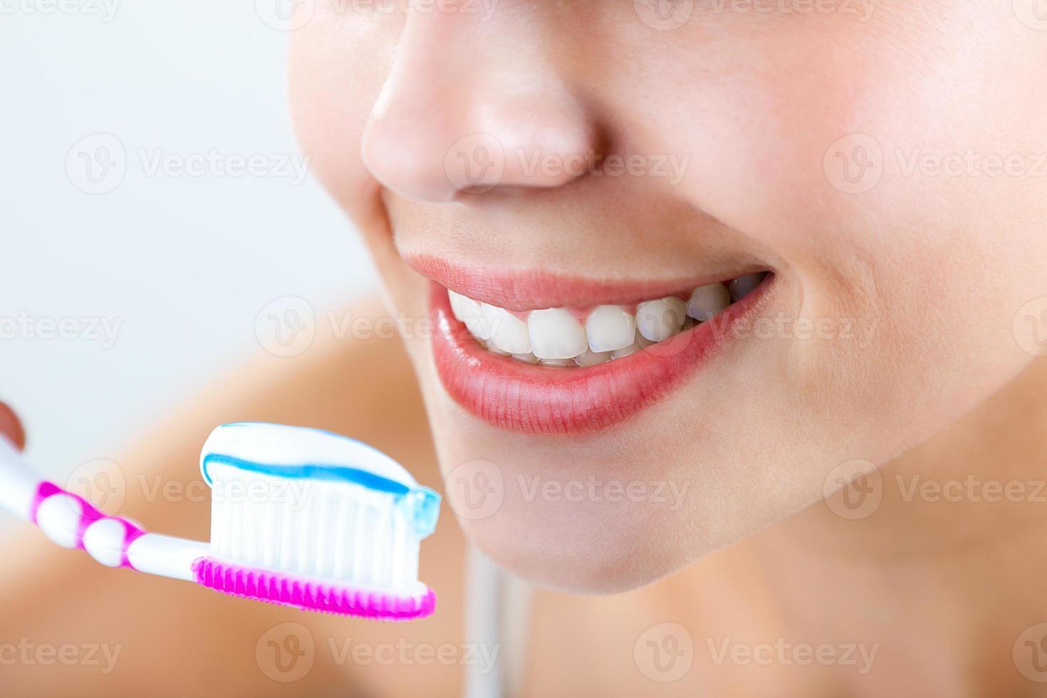 mulher jovem e bonita palitando os dentes. foto