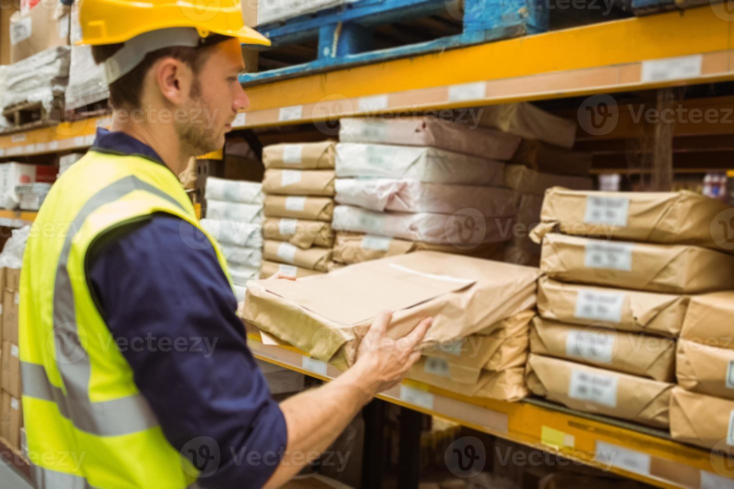 trabalhador de armazém, levando o pacote na prateleira foto