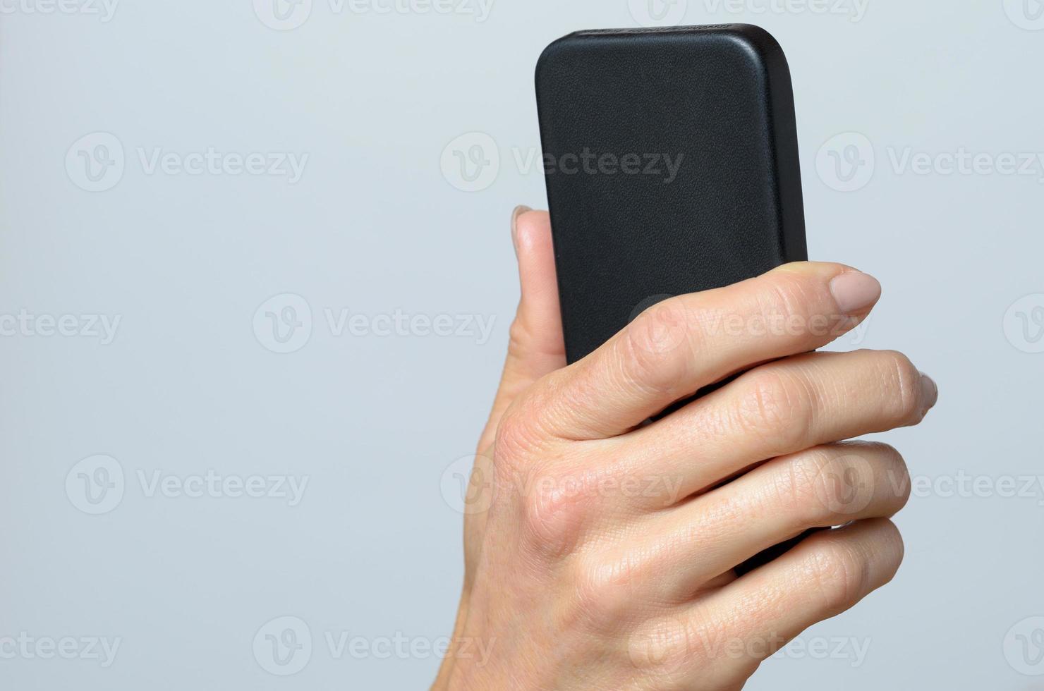 mão segurando um celular preto foto