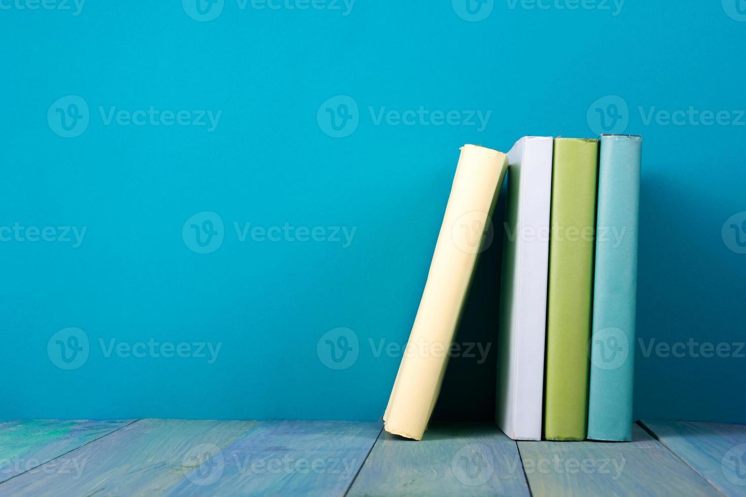 linha de livros, fundo azul sujo, cópia livre espaço foto