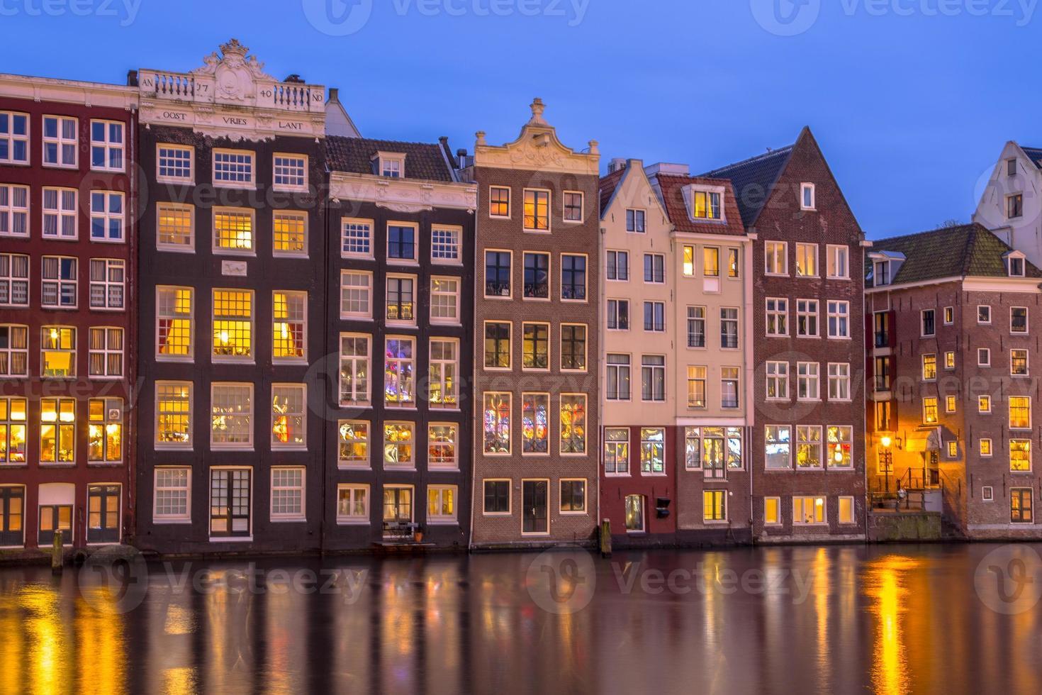 casas de canal em Damrak em Amsterdã foto