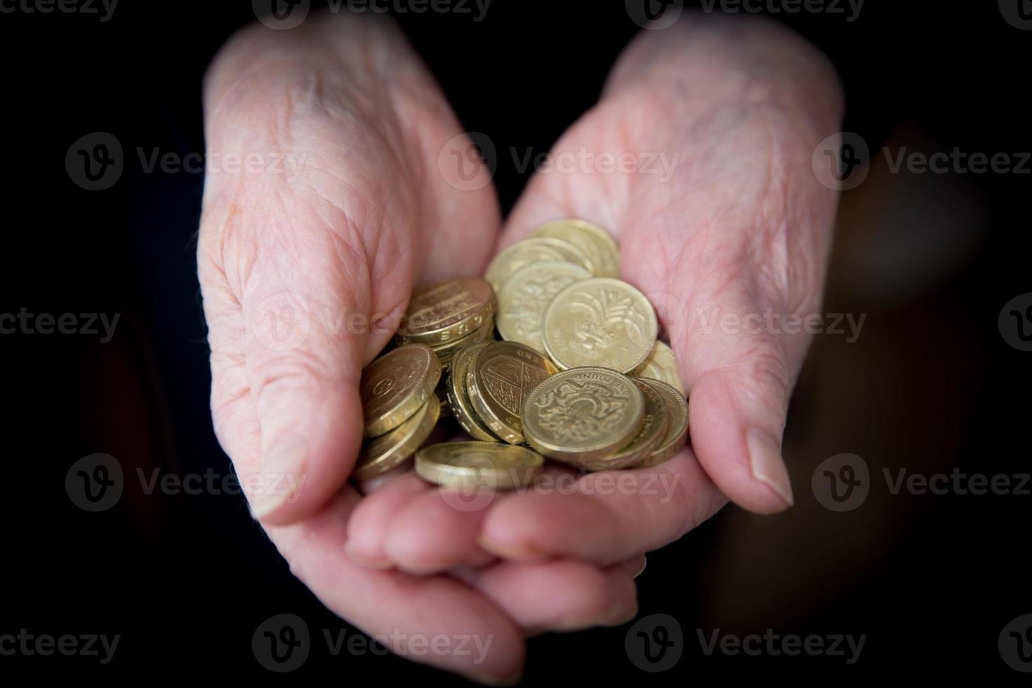 mãos idosas segurando moedas da libra esterlina foto