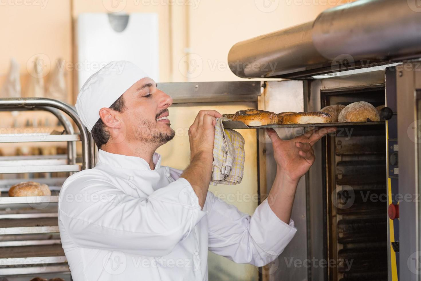 padeiro feliz tirando bagels frescos foto