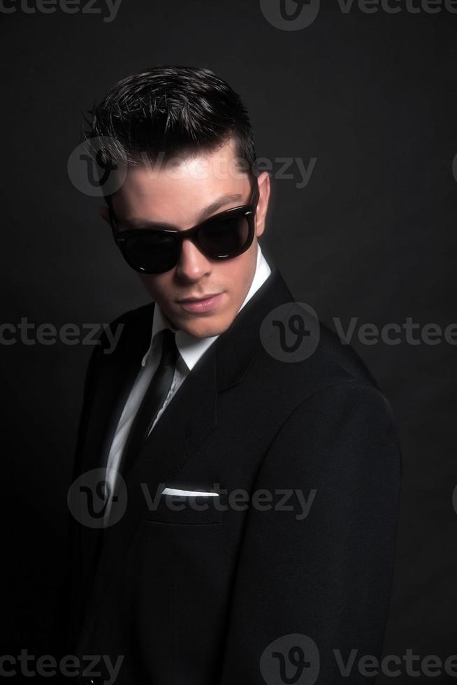 anos 50 retrô moda homem vestindo terno e óculos de sol pretos. foto