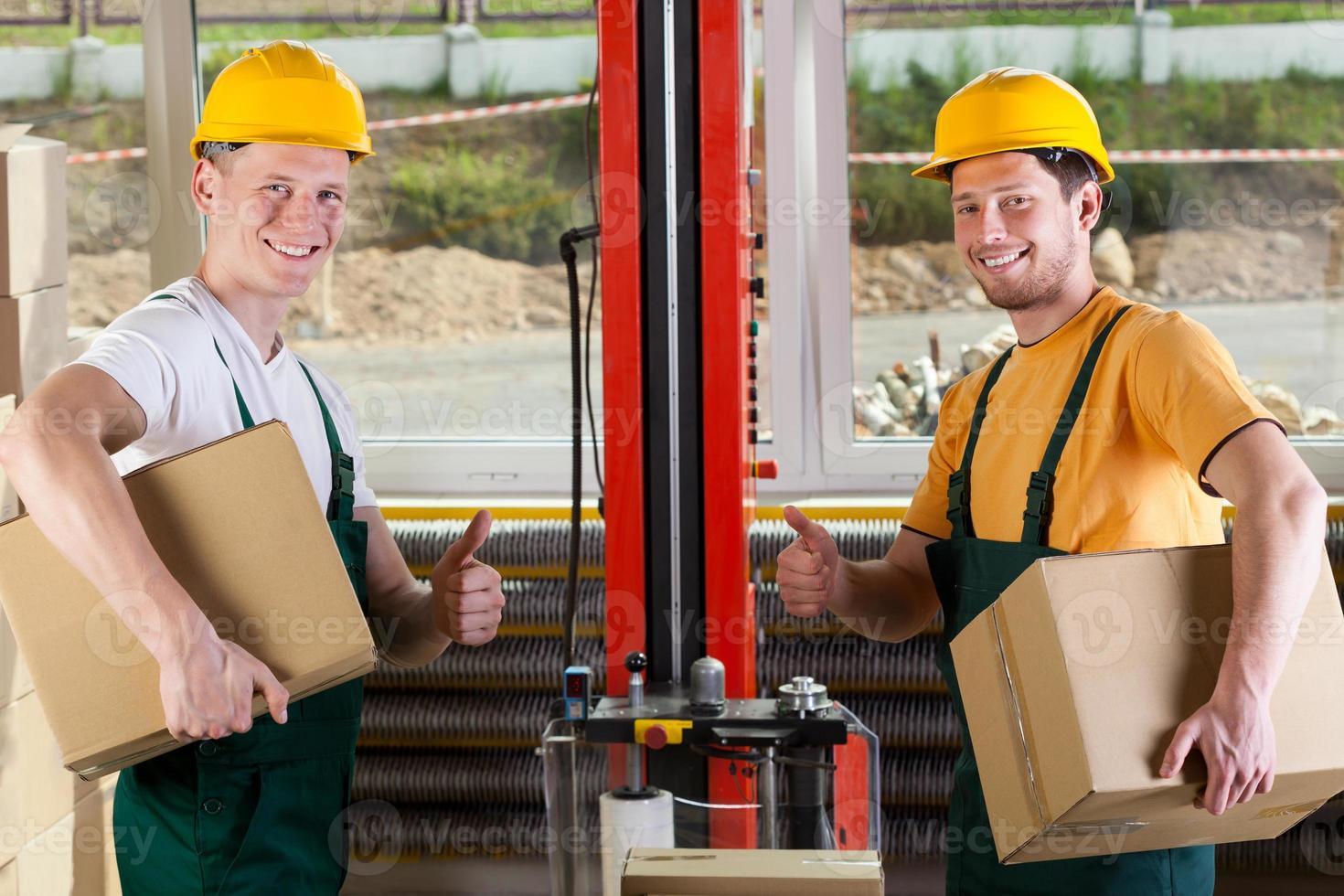trabalhadores de fábrica, mostrando os polegares para cima o sinal foto