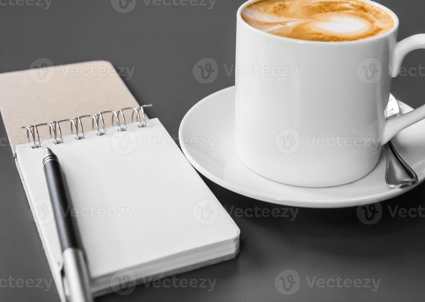 copo de livreto e café em cima da mesa foto