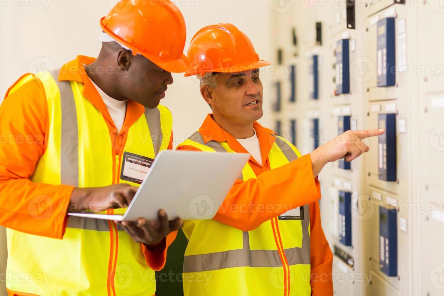 dois eletricistas que verificam a caixa de controle industrial foto