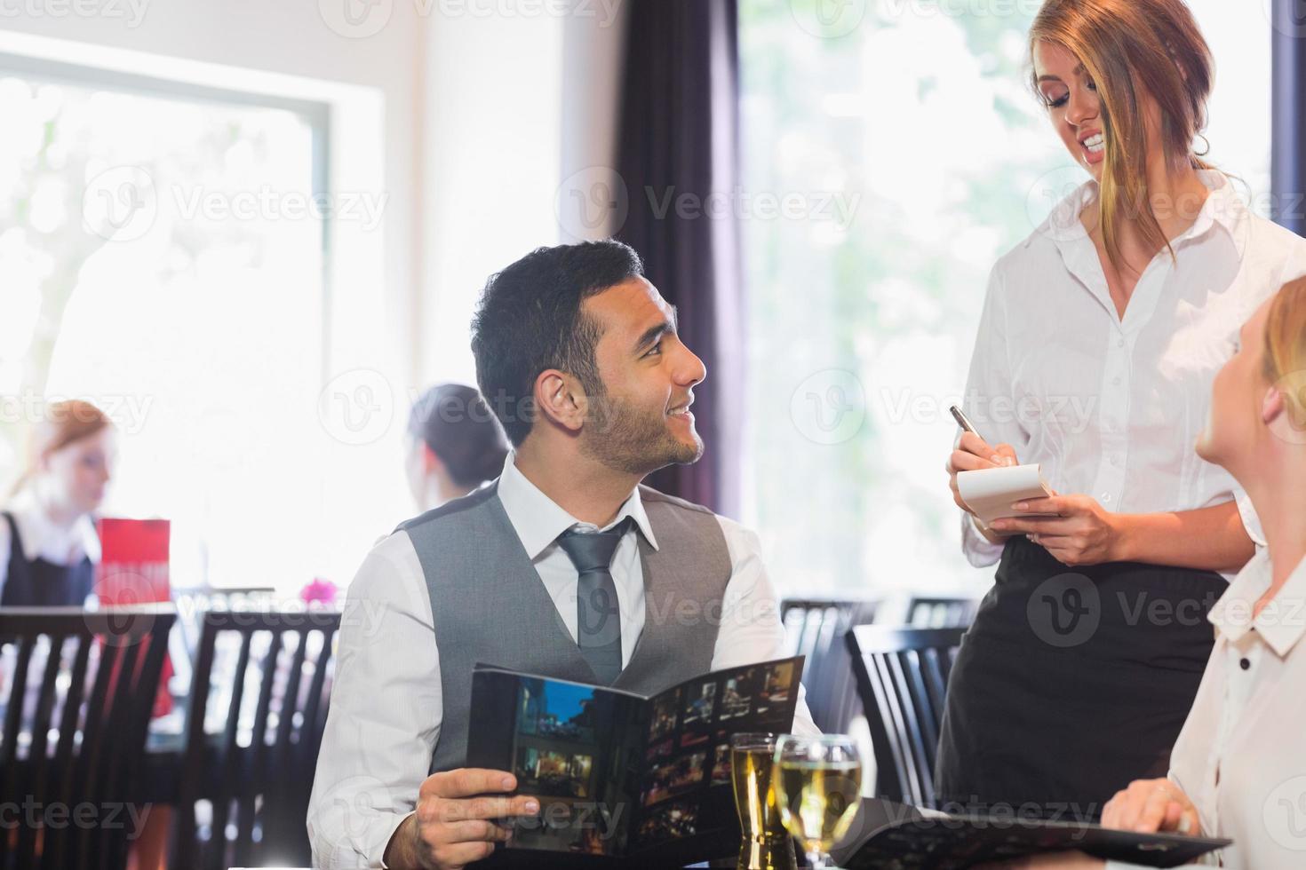 empresário bonito pedir comida de garçonete foto