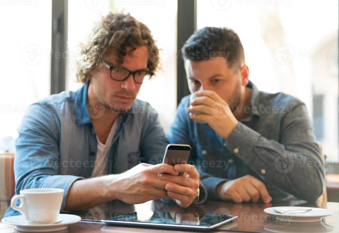 homens casuais em um café, olhando para o telefone móvel foto