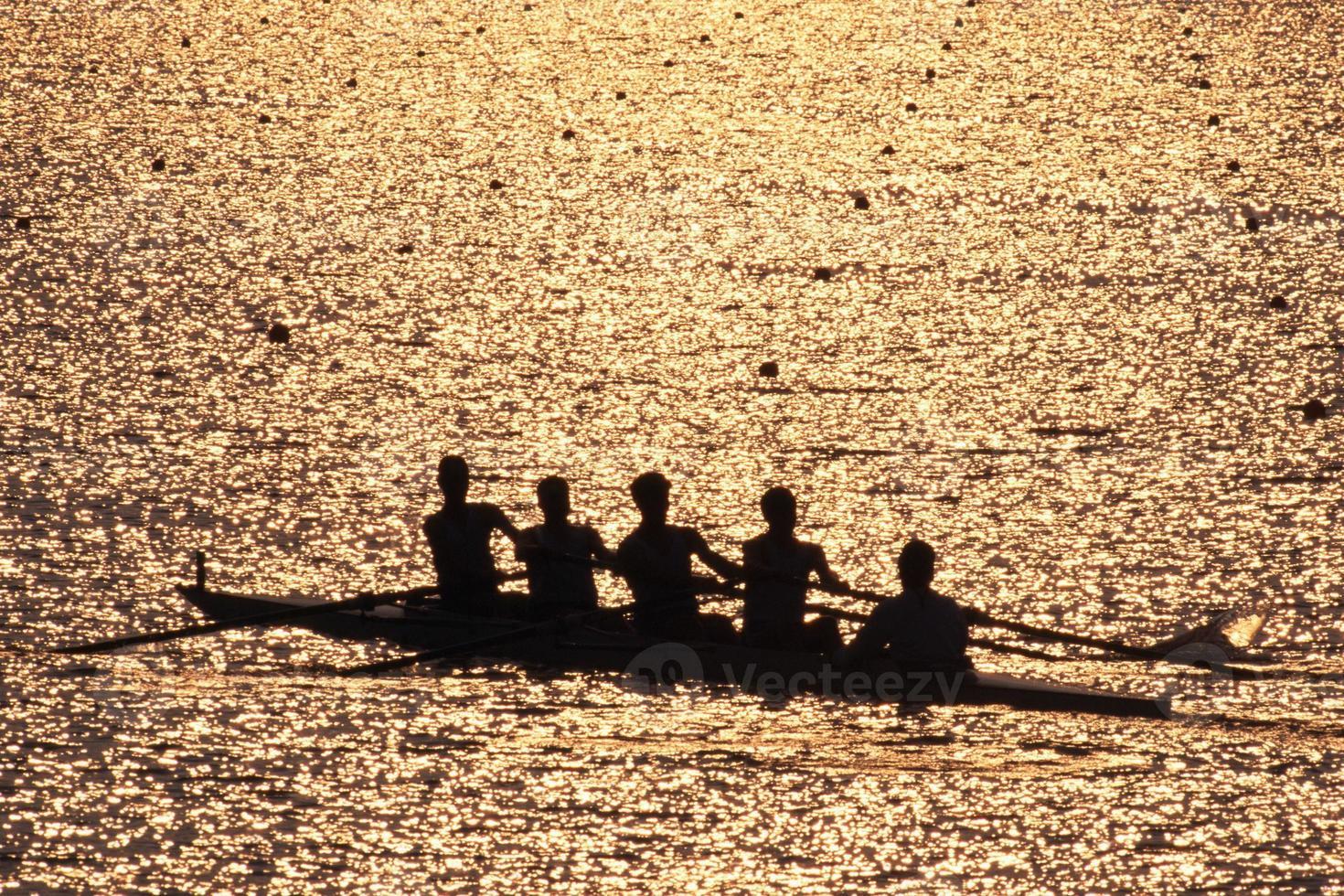 equipe de remadores em silhueta ao pôr do sol foto