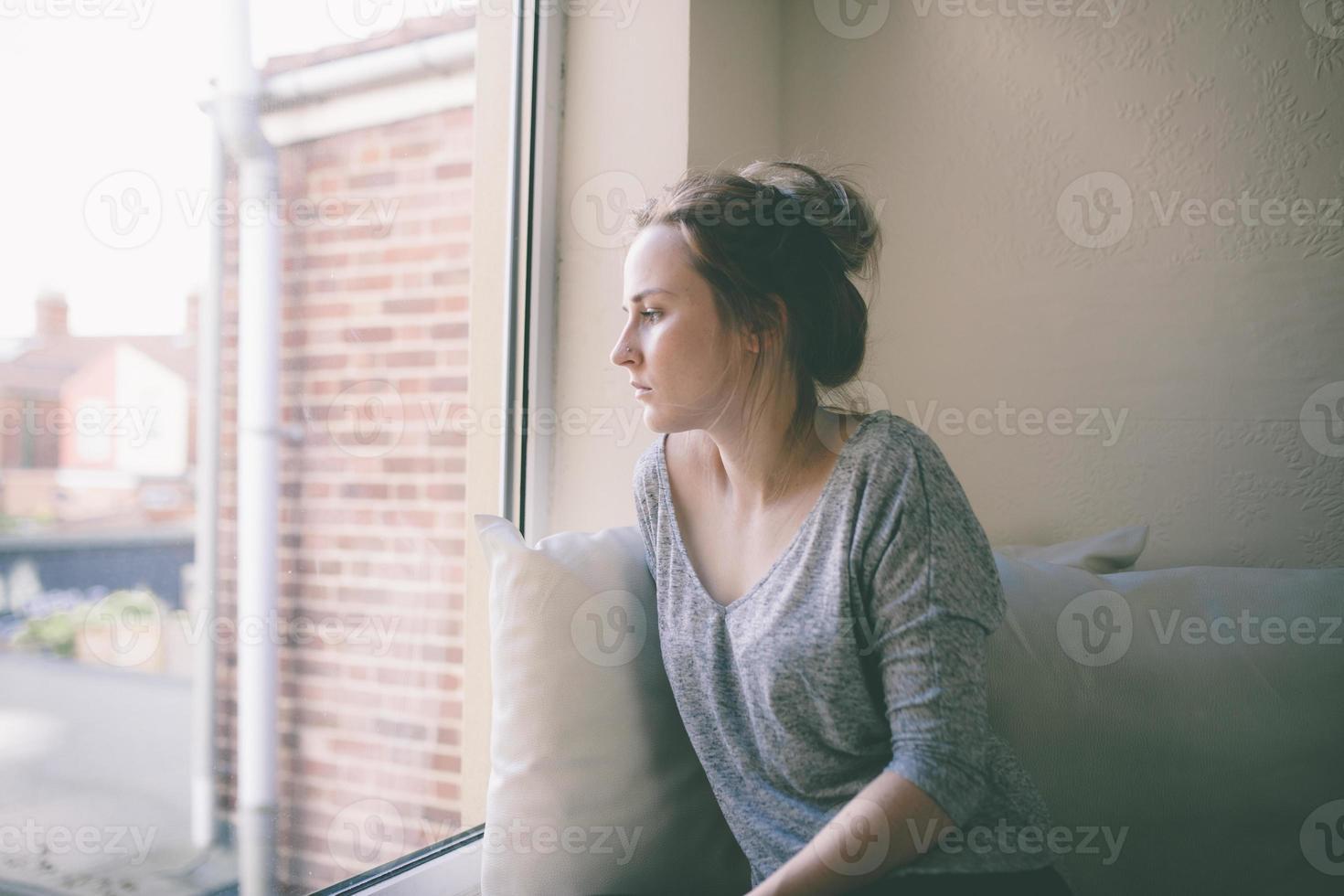 menina loira olhando pela janela foto