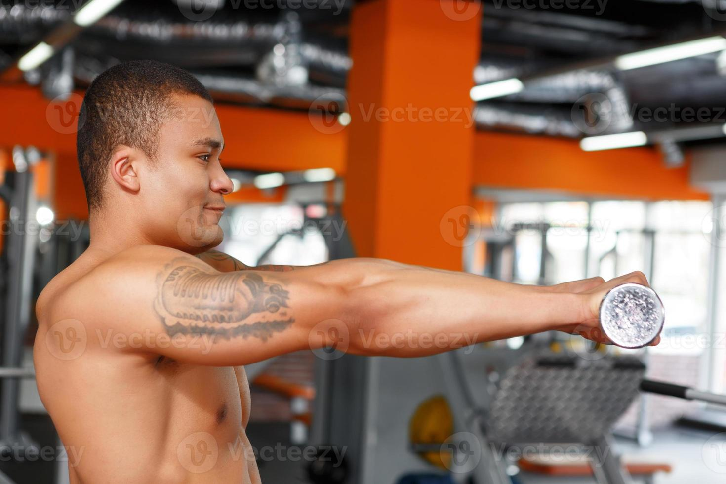 perfil de homem segurando halteres na frente do peito foto