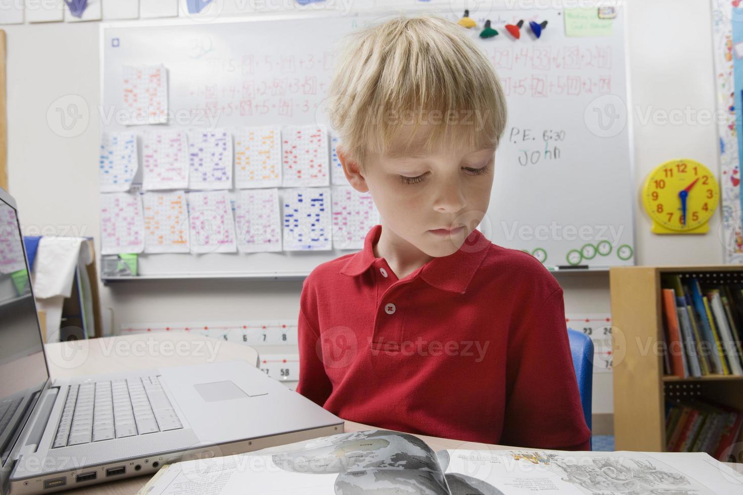 livro de leitura do menino na sala de aula foto