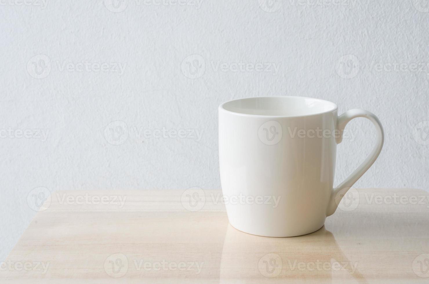 copo branco na mesa de madeira foto