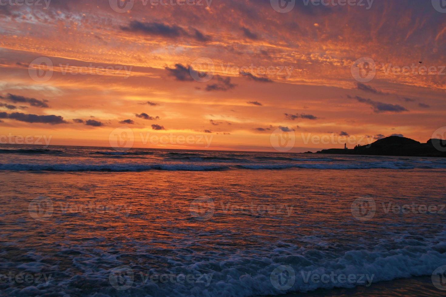 glorioso pôr do sol sobre o farol e o mar foto