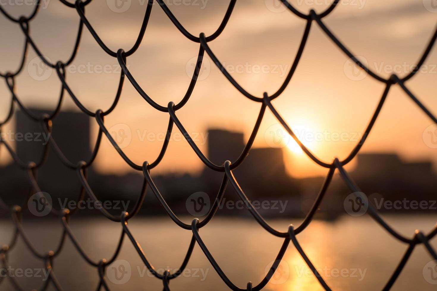 pôr do sol através da cerca foto