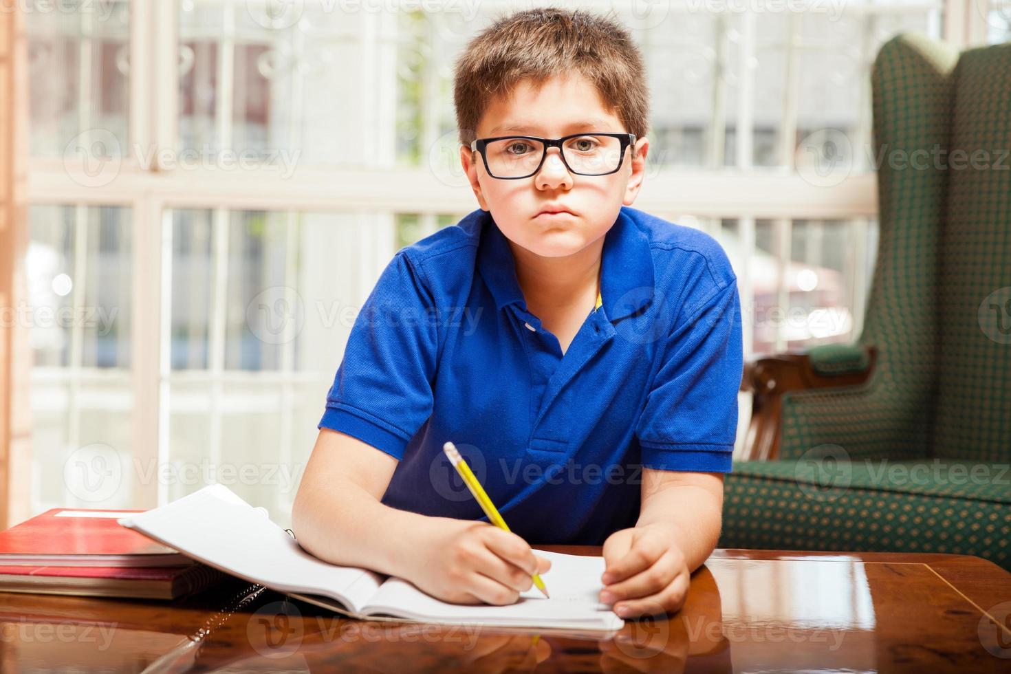 garoto fazendo alguns trabalhos de casa foto