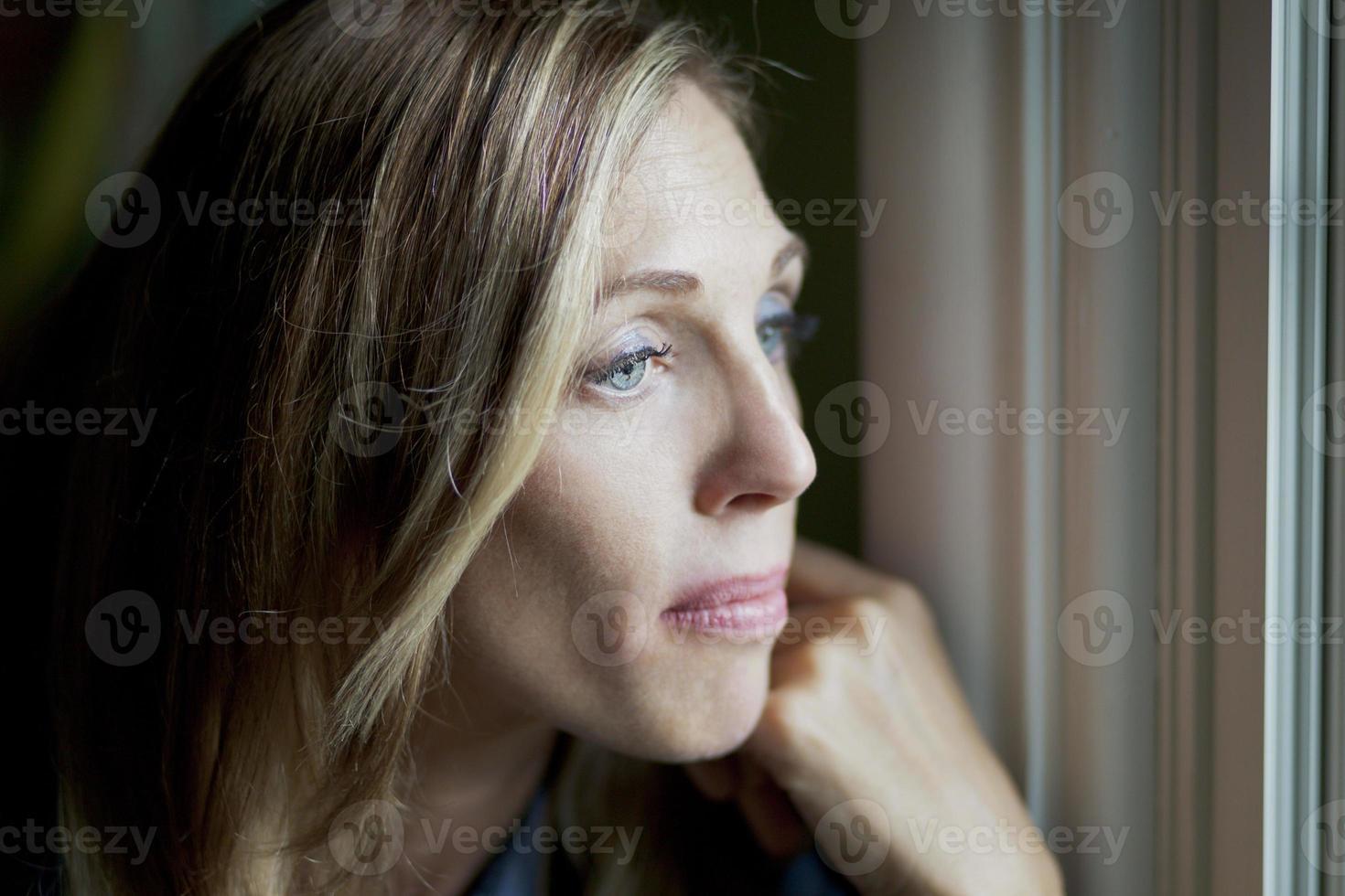 mulher triste na janela foto