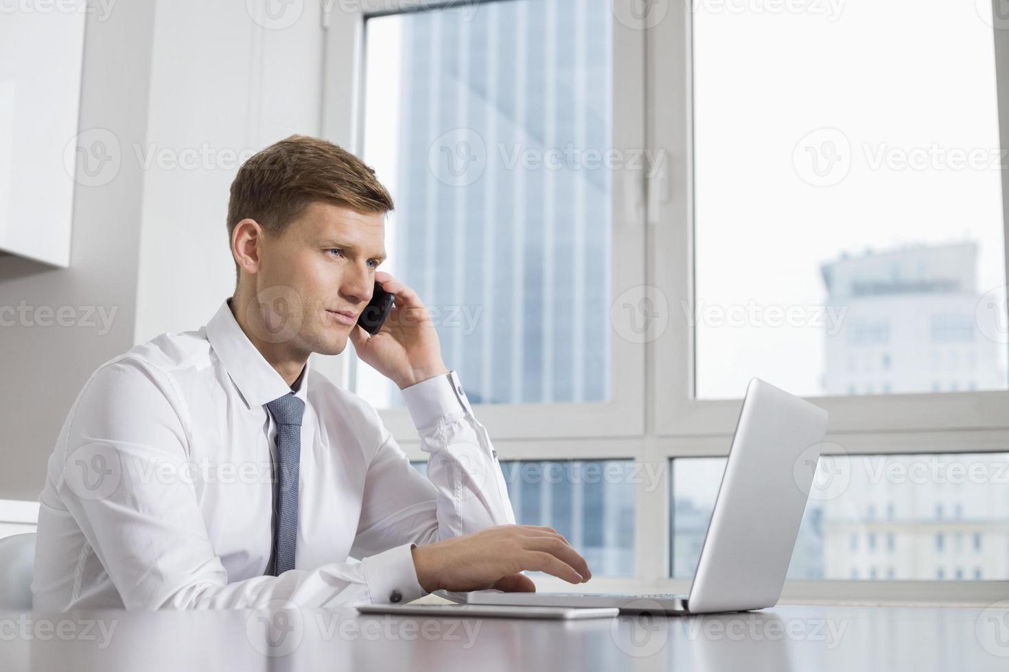 empresário adulto médio plantão enquanto estiver usando o laptop em casa foto