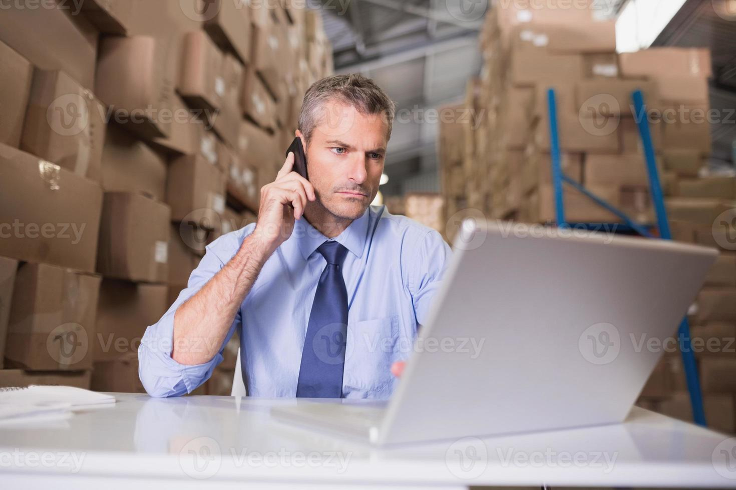 gerente de armazém, usando telefone celular e laptop foto