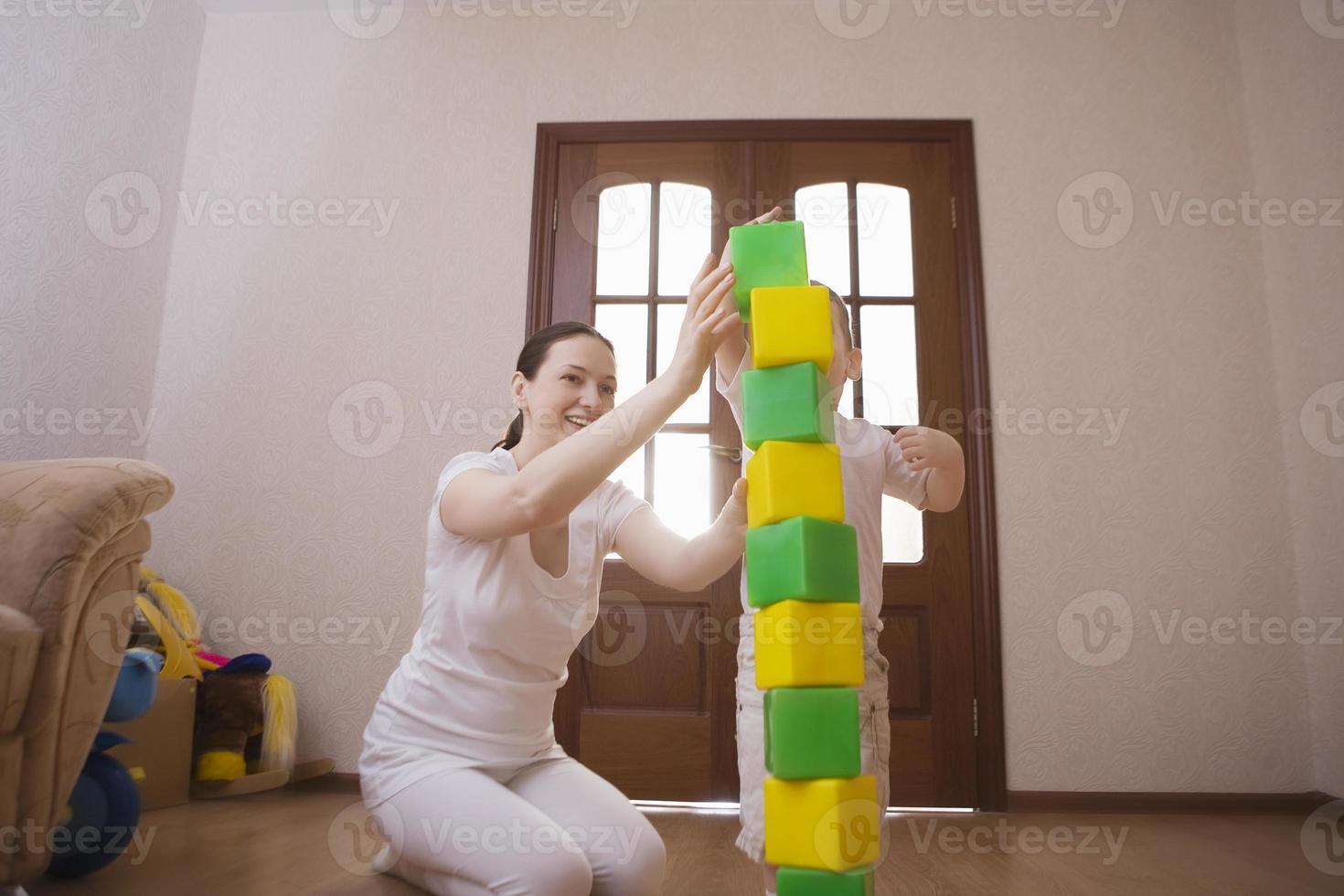 mãe e filho, construção de torre de cubos coloridos foto