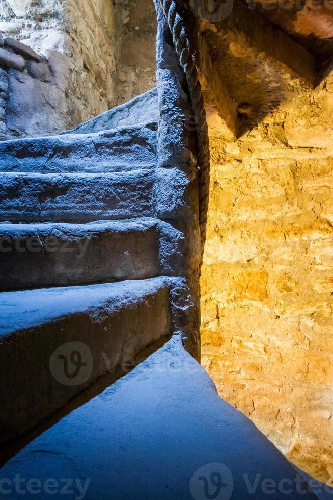 escada em espiral de pedra com luz mista no castelo foto