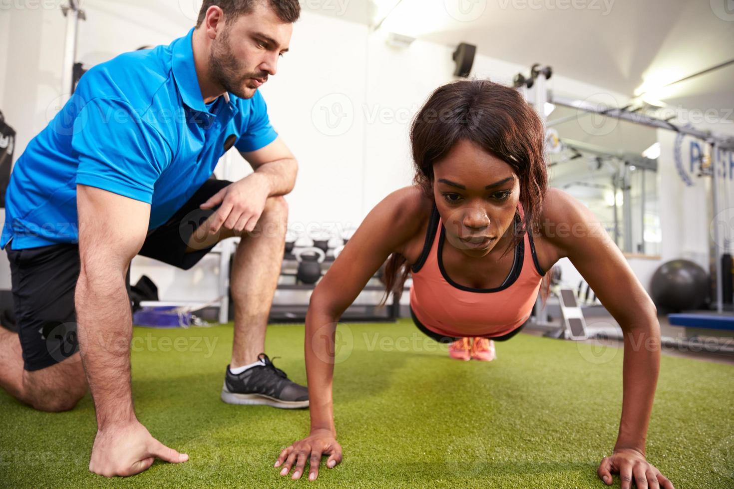 jovem mulher fazendo flexões sob a supervisão de um treinador foto