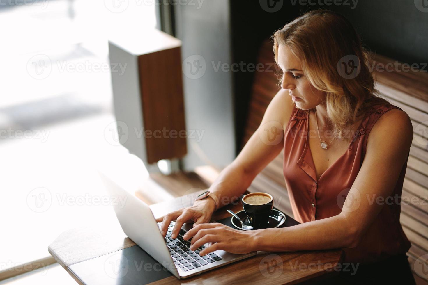 mulher que trabalha em um computador laptop em uma cafeteria foto