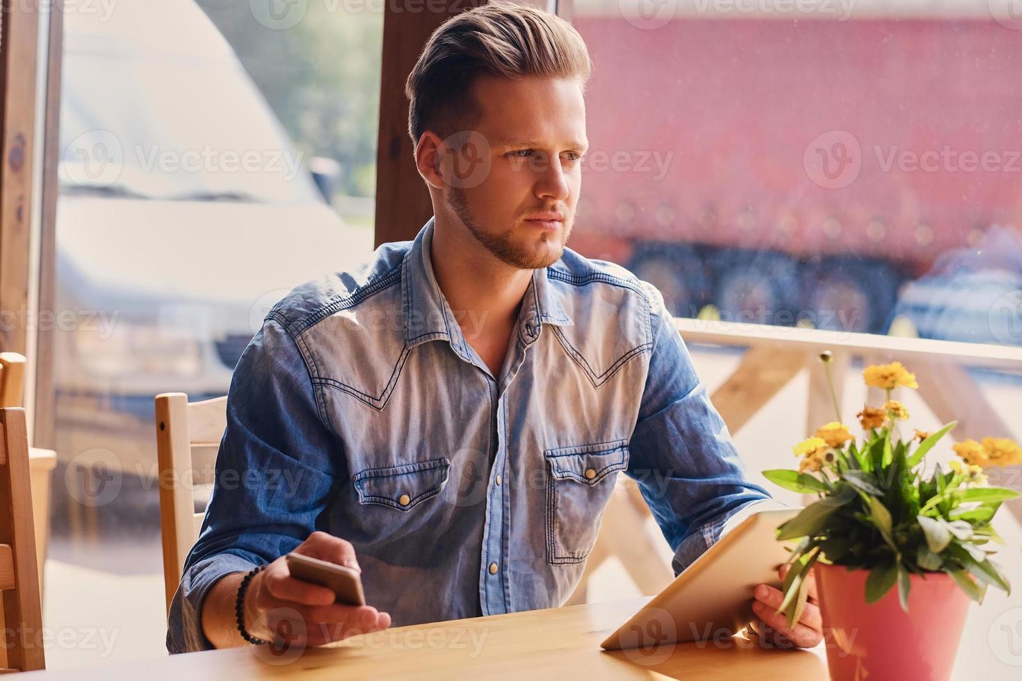 um homem usando um tablet pc e smartphone no café. foto