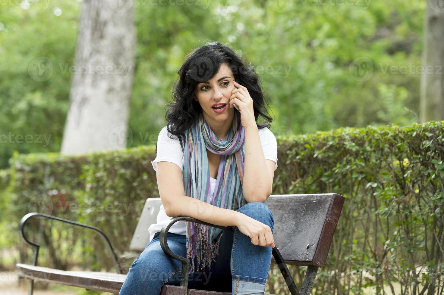 feliz mulher latina atraente vestindo roupas casuais, sentado em um banco de parque mensagens de texto e falando em seu telefone móvel inteligente em um parque verdejante ou prados foto