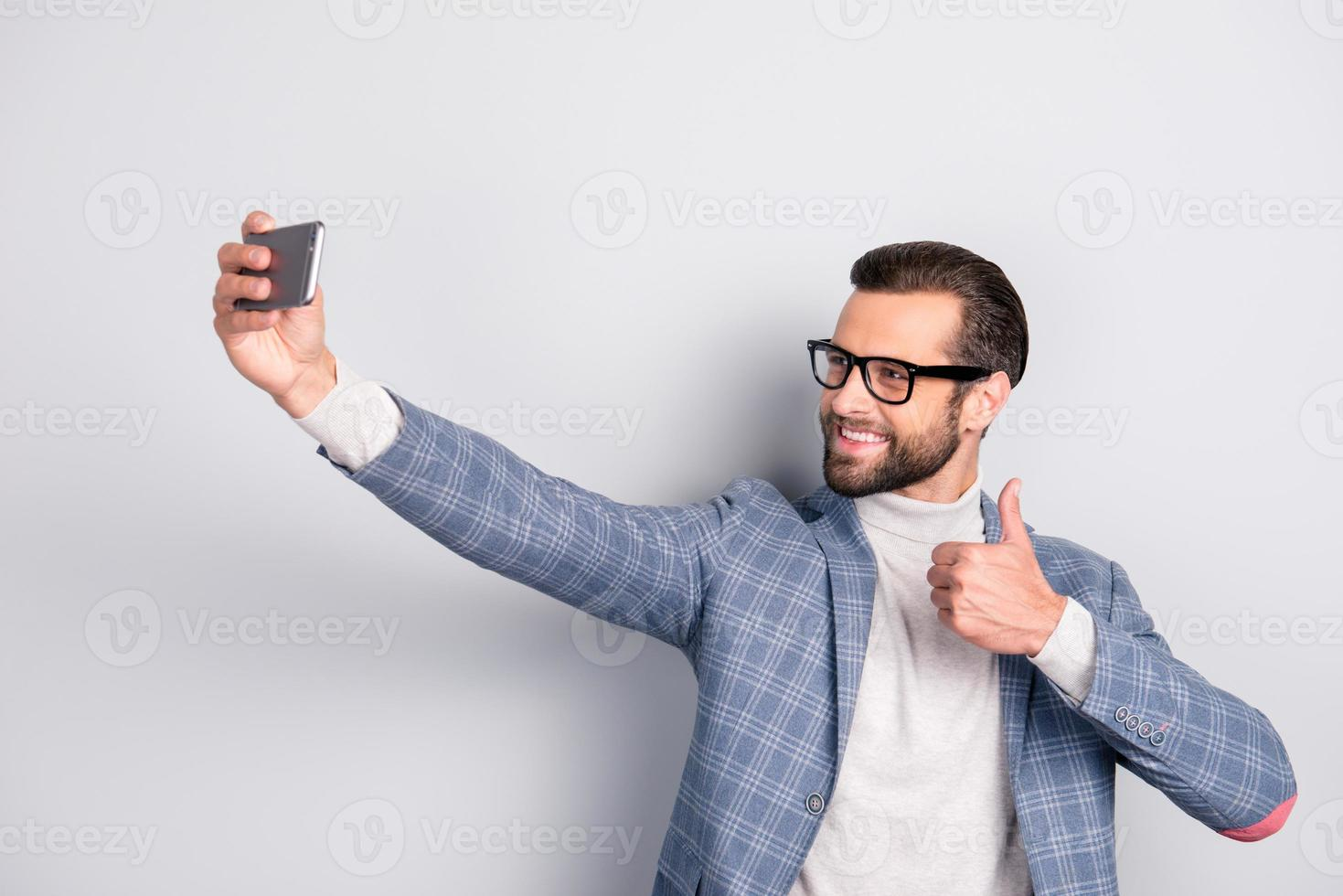 viril, dura, educação, homem atraente com barba no casaco tiro auto foto na câmera frontal do telefone inteligente sobre fundo cinza, aparecendo o polegar, tendo videochamada