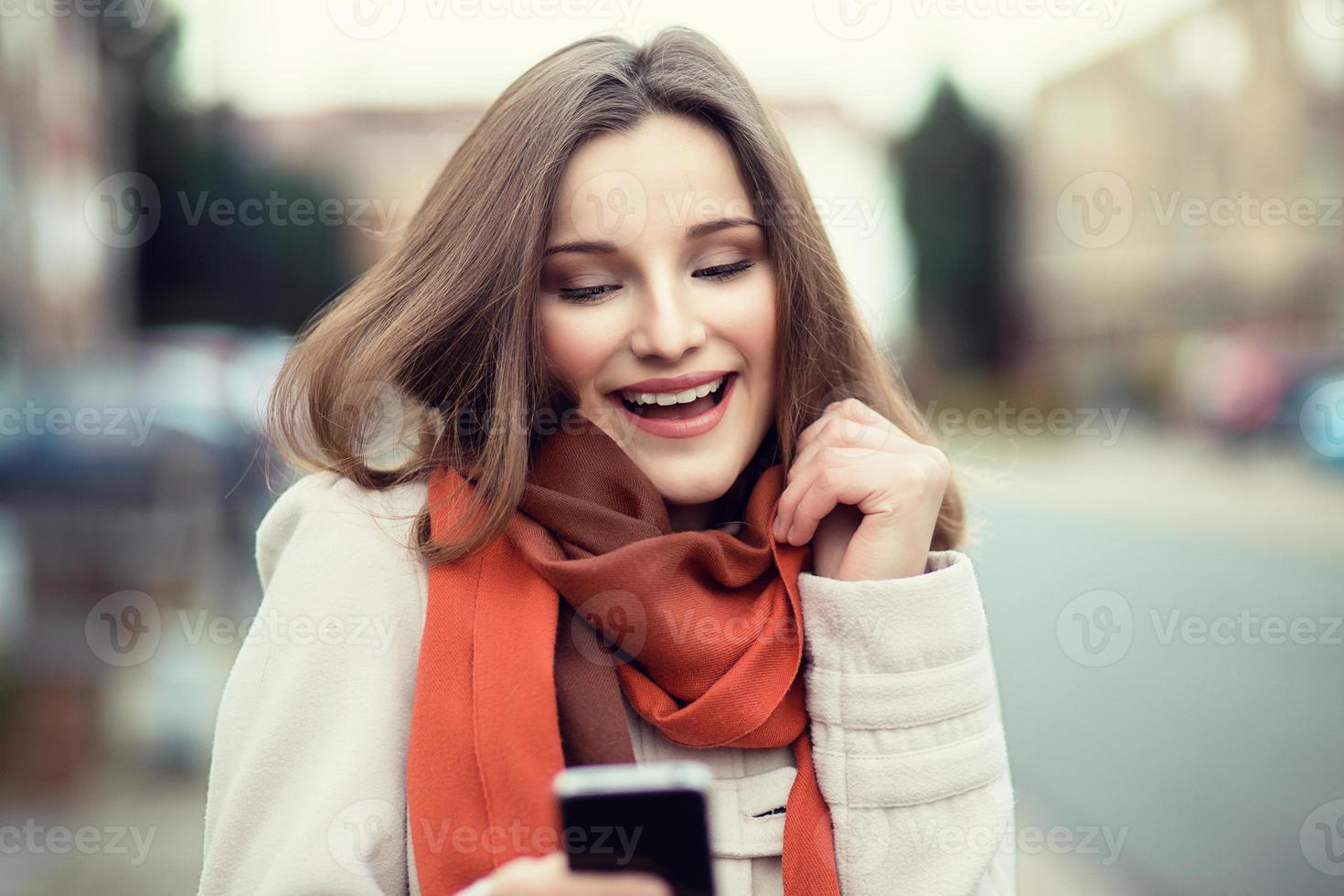 mensagens de mulher. closeup jovem feliz sorridente alegre mulher bonita menina olhando para celular móvel lendo envio sms isolado cityscape ao ar livre fundo. expressão positiva do rosto emoção humana. multicultural, raça mista, modelo russo asiático foto