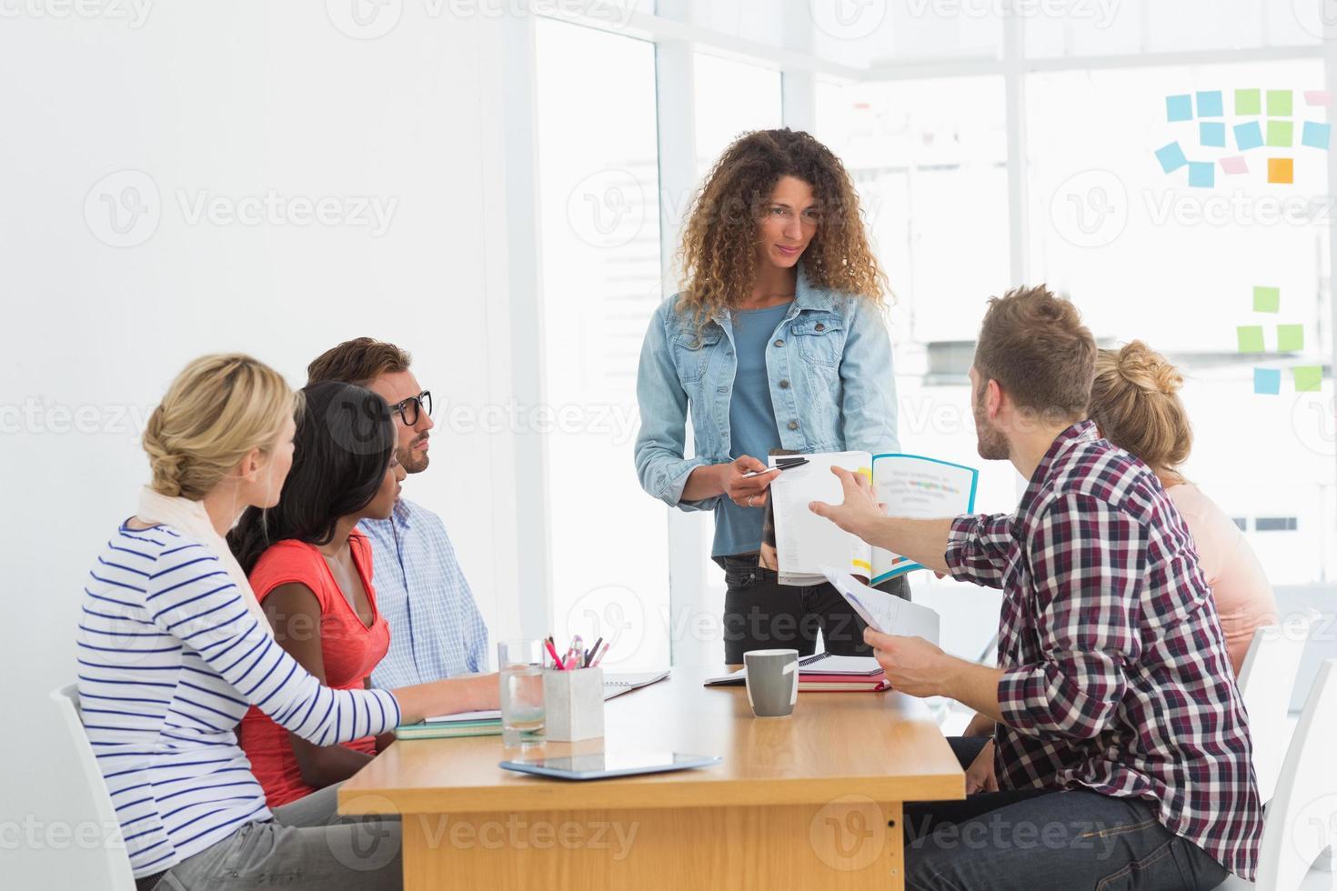 mulher apresentando idéias para jovens designers, tendo uma reunião foto