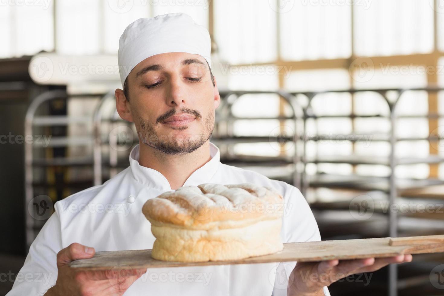 padeiro, cheirando um pão fresco foto