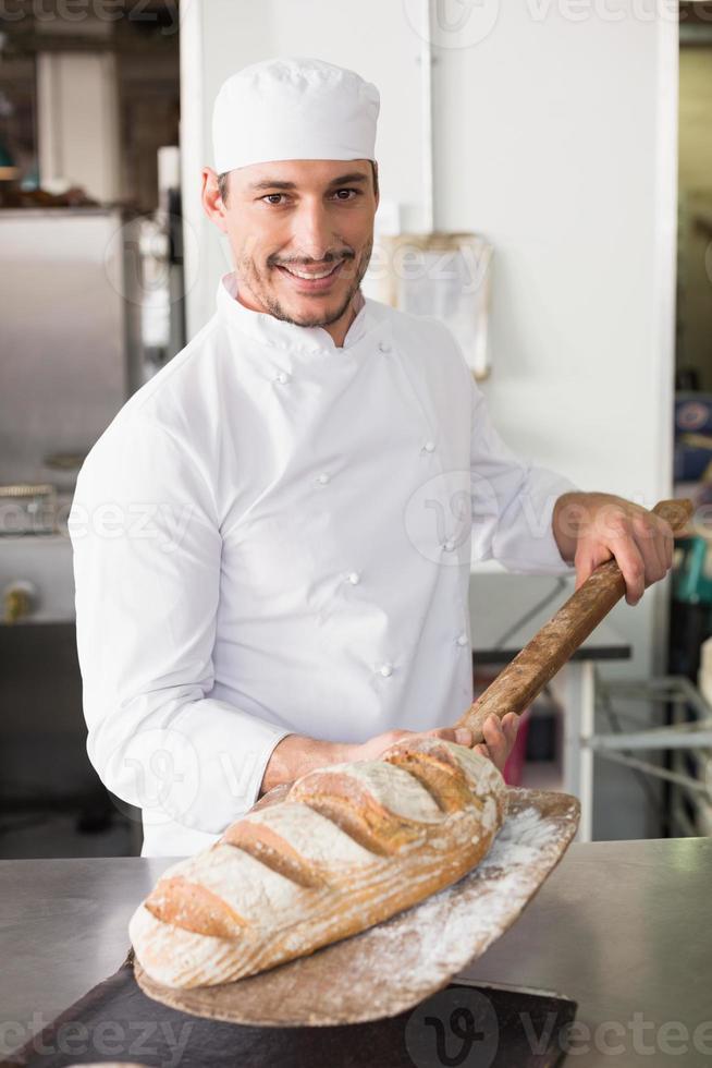 padeiro feliz tirando pão fresco foto