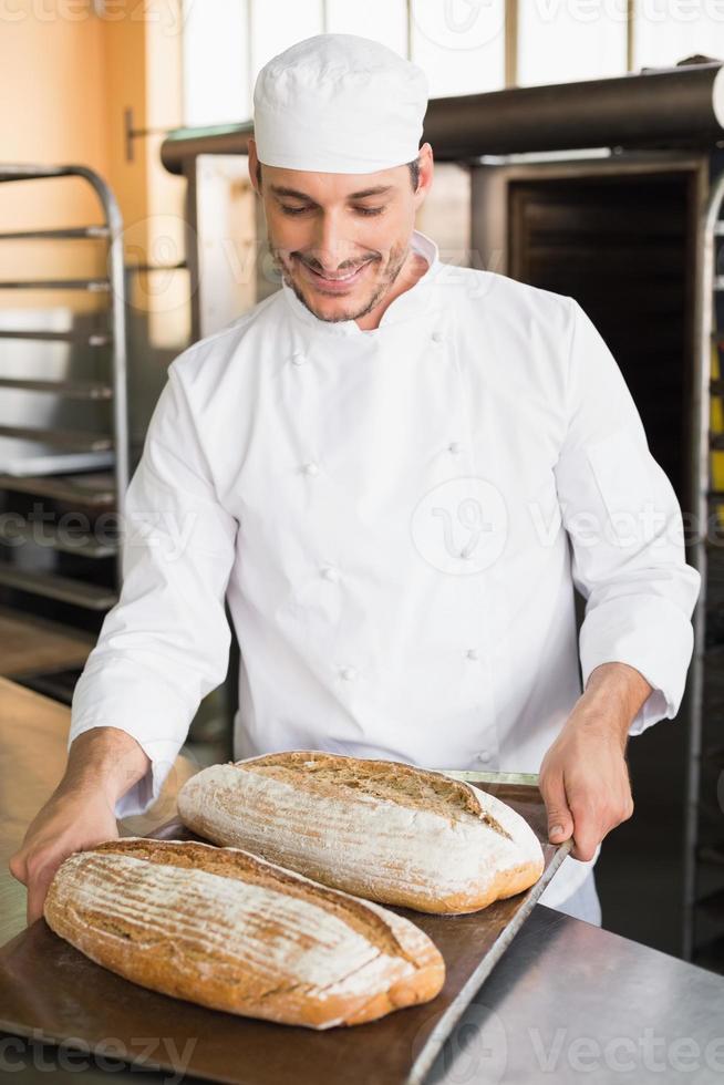 padeiro feliz segurando a bandeja de pão fresco foto