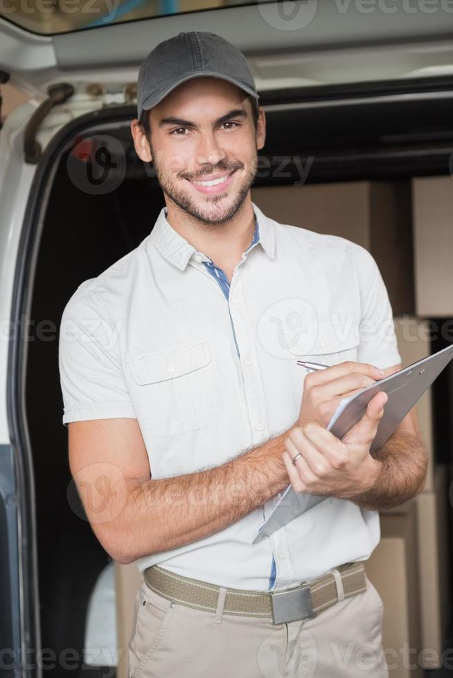 motorista de entrega sorrindo para a câmera ao lado de sua van foto