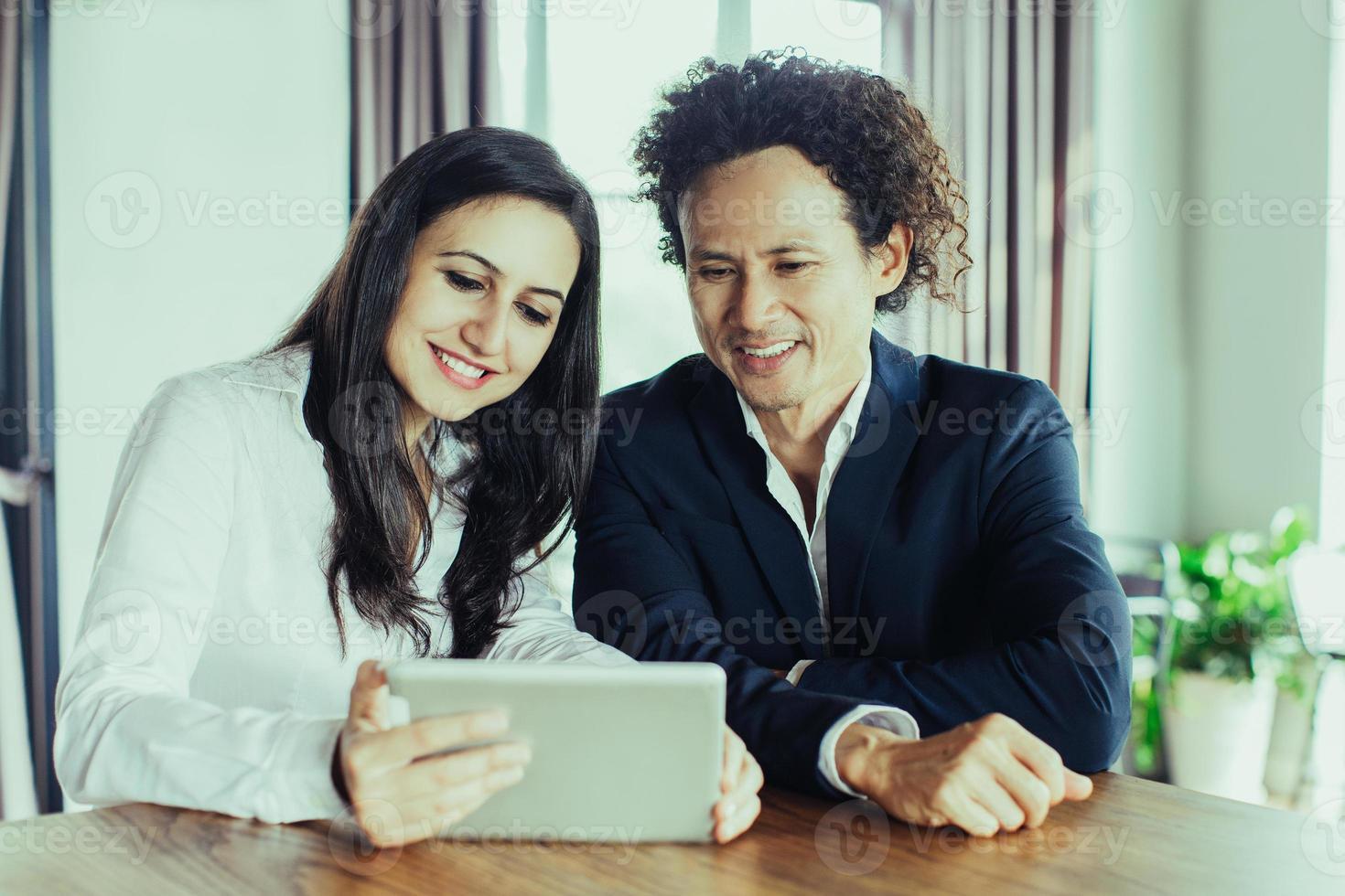 empresários alegres discutindo dados sobre tablet foto