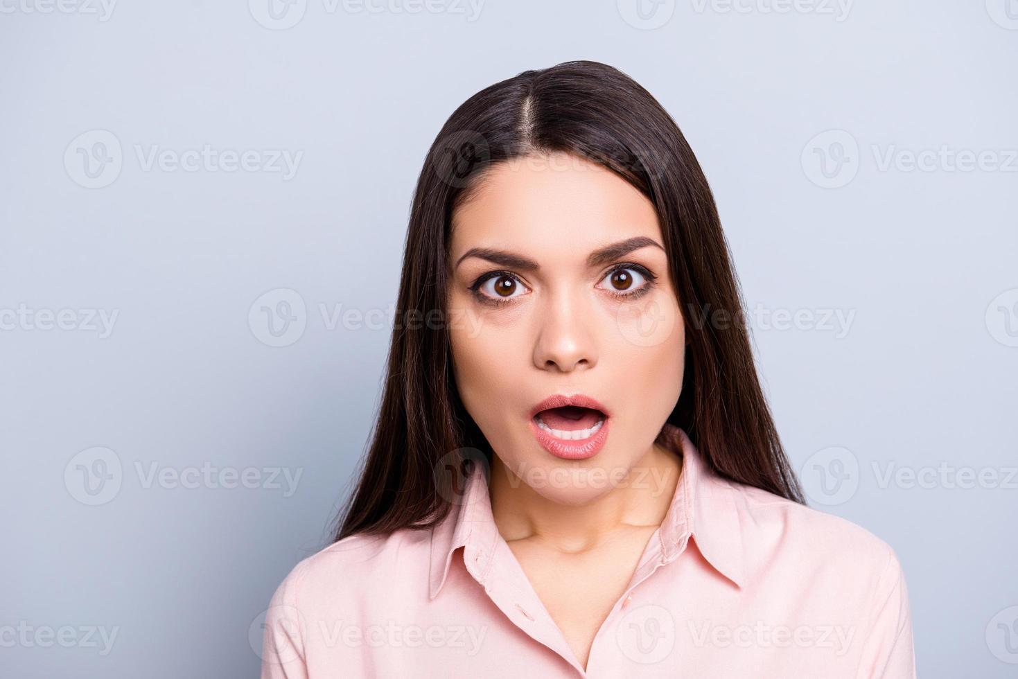 retrato de mulher chocada, assustada, com medo, impressionada, estressada e inesperada em camisa clássica com olhos de boca aberta, olhando para a câmera isolada em fundo cinza foto