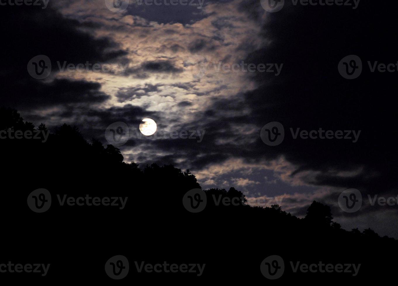 paisagem de noite com a lua em um fundo de montanhas foto