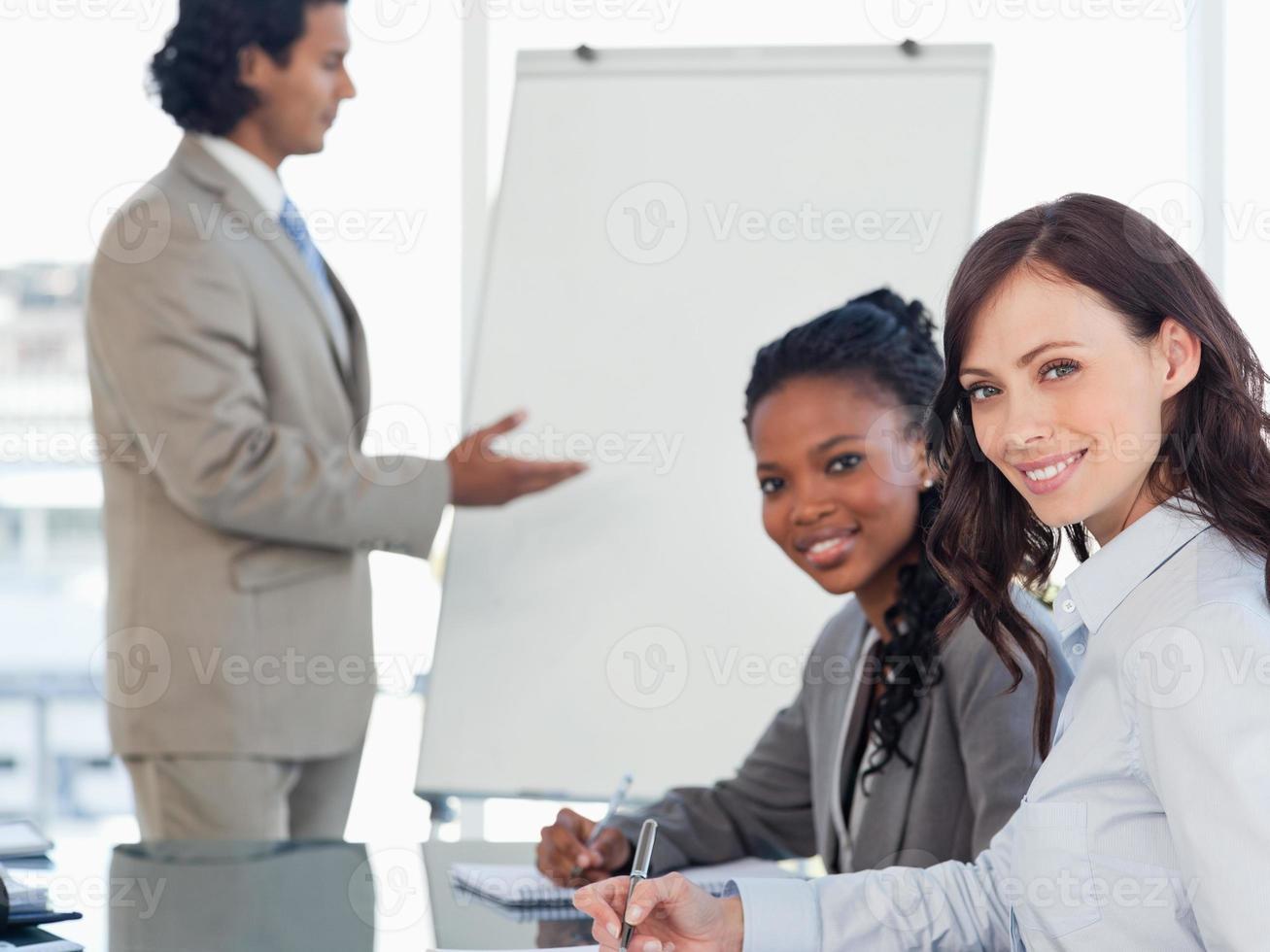 dois jovens funcionários sorridentes trabalhando enquanto ouve uma apresentação foto